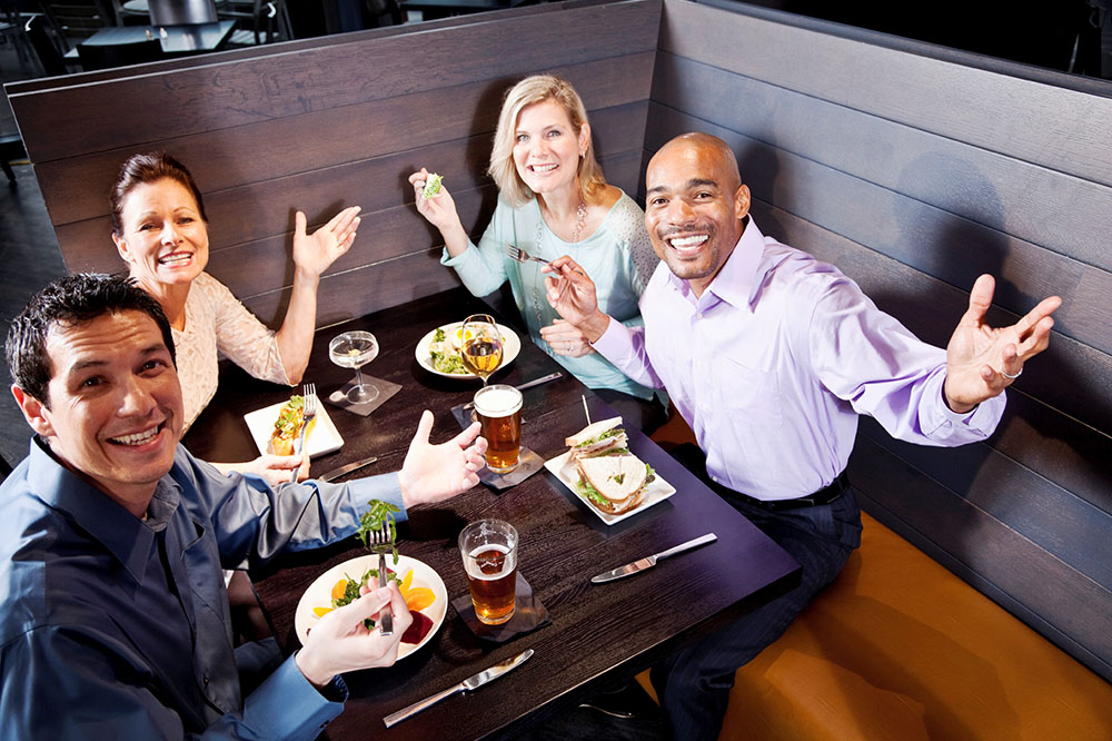 Two multi-ethnic couples eating, drinking and talking in restaurant.