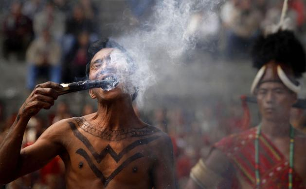 A Naga fire-eater bites a burning wood on the second day of the Hornbill festival in Kisama village, on the outskirts of Kohima, India, Friday, Dec. 2, 2011. The festival is held to promote cultural heritage of the Nagas, an ethnic group that live in northeastern region of India, bordering Myanmar. (AP Photo/Anupam Nath)