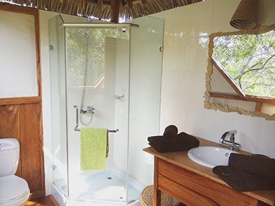 Showering while watching the monkeys and birds in the bush – the real Africa feeling